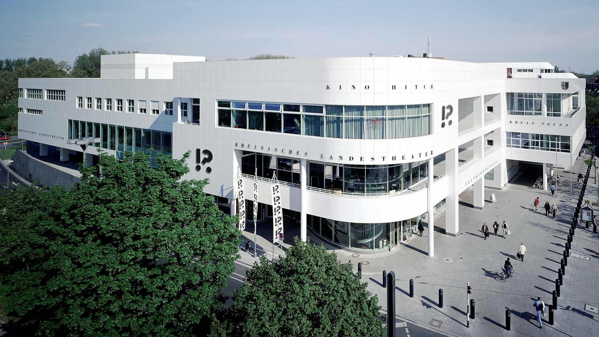 Außenansicht des Rheinischen Landestheater Neuss mit dem Dramaticon-Logo von Johannes López Ayala an Fassade und Beflaggung